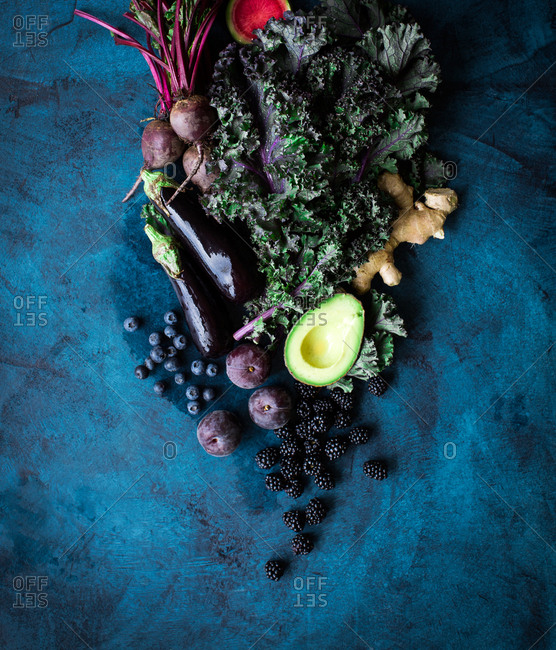 Raw fruits and vegetables on dark background