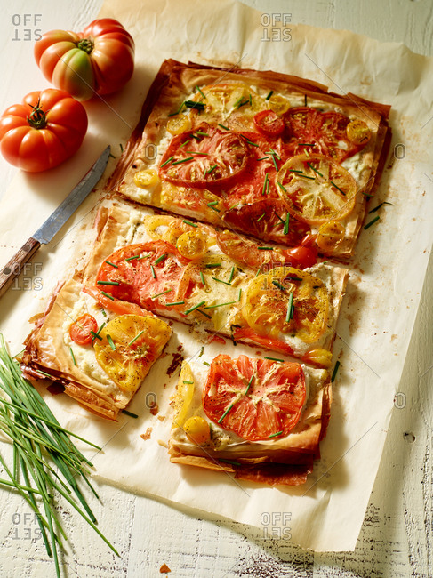 Pizza with heirloom tomatoes and chives and a knife
