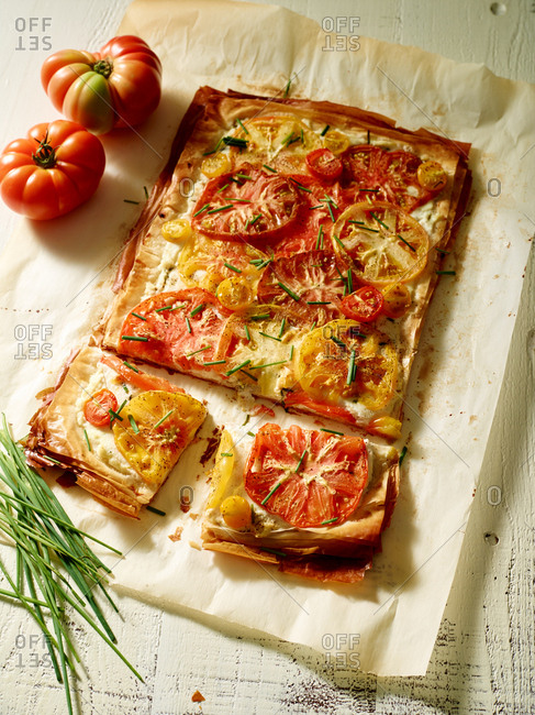 Sliced pizza with heirloom tomatoes and chives