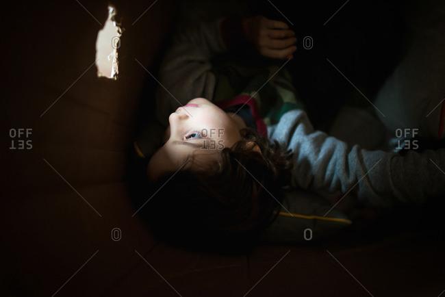 Boy looking through hole in box