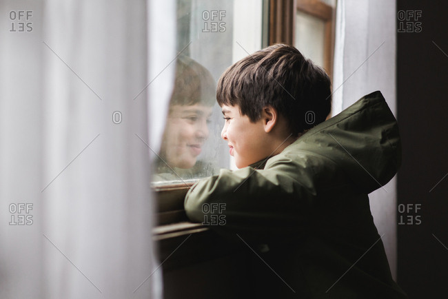 Boy reflected in window smiling