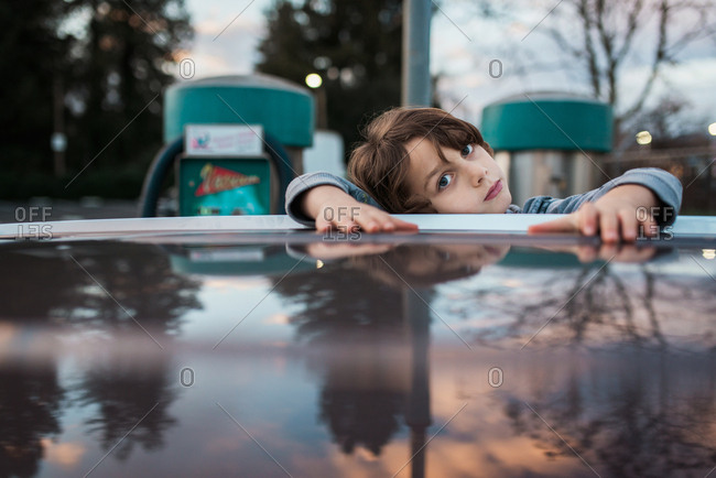Boy resting head on car roof