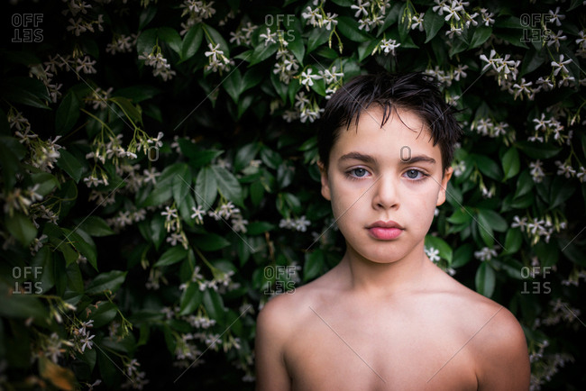 Shirtless boy standing by flowering bush
