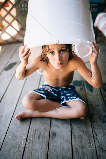 Boy covering himself with bucket