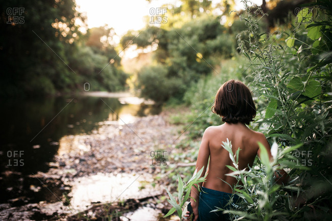 Boy by plants looking at river