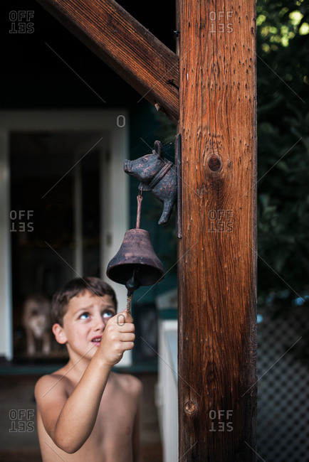 Boy ringing a bell on porch