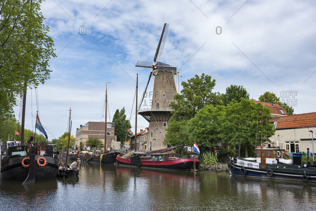 June 10, 2017: Netherlands- Gouda- harbor with traditional sailing ships and wind mill