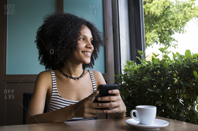 Young woman with smartphone sitting in a coffee shop looking out of window