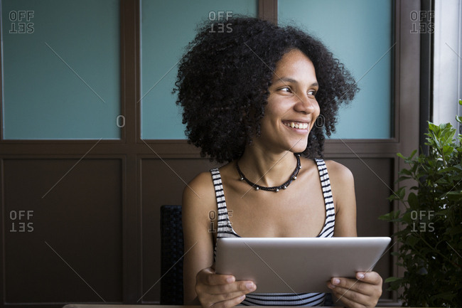 Smiling young woman with tablet sitting in a coffee shop