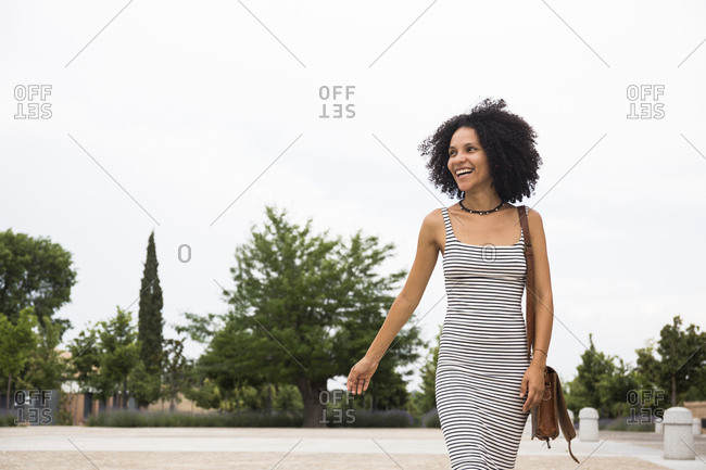 Laughing young woman with shoulder bag