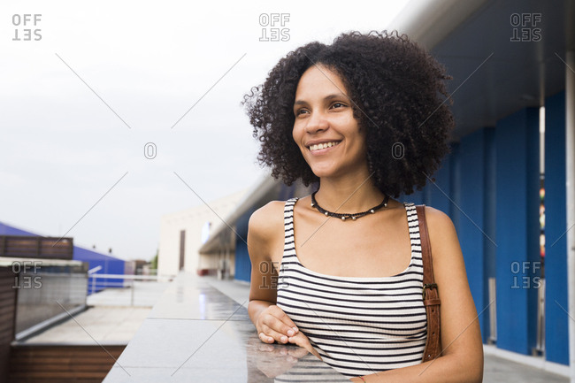 Portrait of smiling young woman leaning on a wall