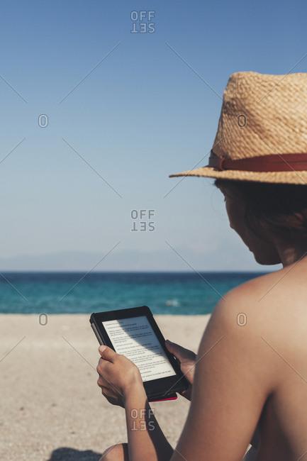 Greece- young woman on the beach reading e-book