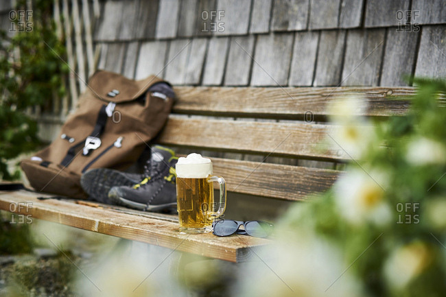 Germany- Bavaria- glass of beer- backpack- sunglasses and hiking shoes on wooden bench