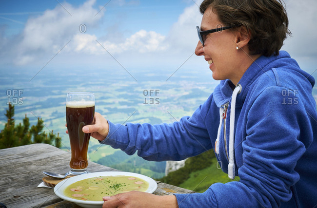 Germany- Chiemgau- happy hiker on Hochfelln with glass of beer and dish of pea soup