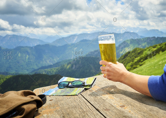 Germany- Chiemgau- hand of hiker on Hochfelln Mountain holding glass of beer- partial view