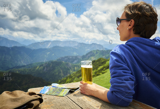 Germany- Chiemgau- hiker on Hochfelln Mountain with glass of beer looking at view