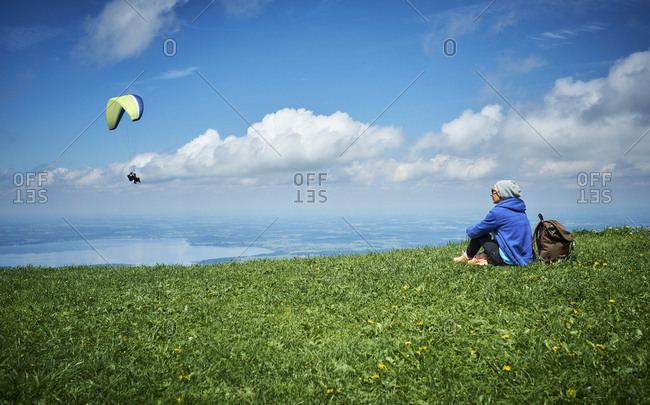 Germany- Chiemgau- hiker sitting on Alpine meadow watching paraglider