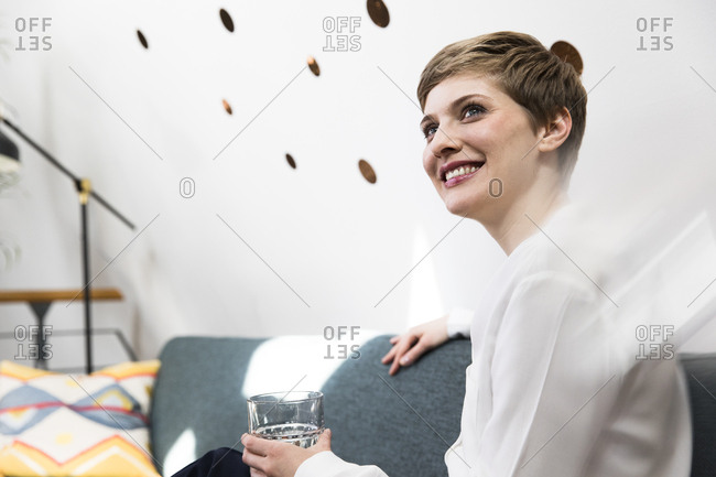 Smiling woman holding glass of water on couch