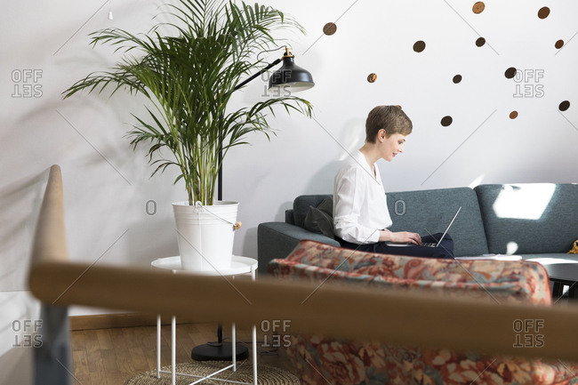 Woman using laptop on couch in modern office