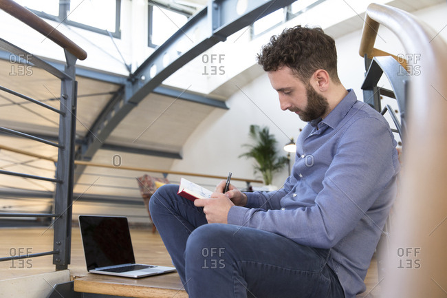 Man in modern office sitting on stairs taking notes