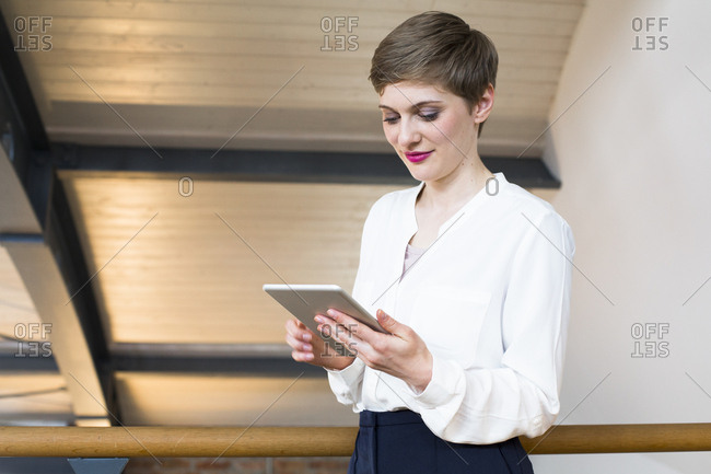 Smiling businesswoman looking at tablet