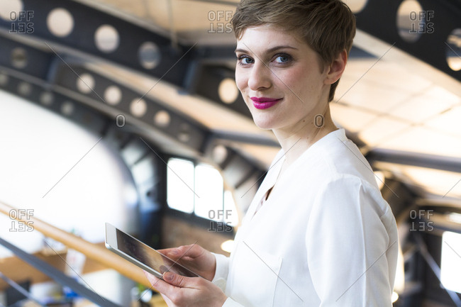 Portrait of smiling businesswoman holding tablet