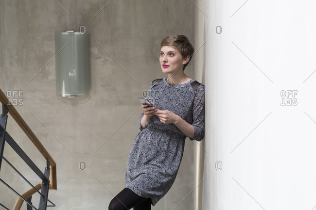 Woman holding cell phone leaning against concrete wall