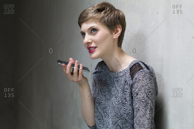 Woman using cell phone at concrete wall