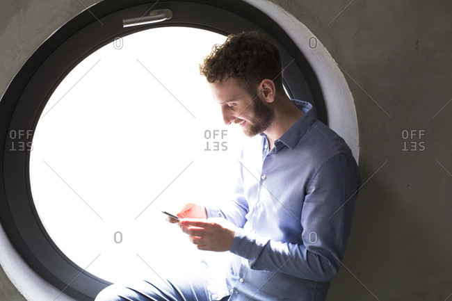 Smiling man sitting in round window looking at cell phone