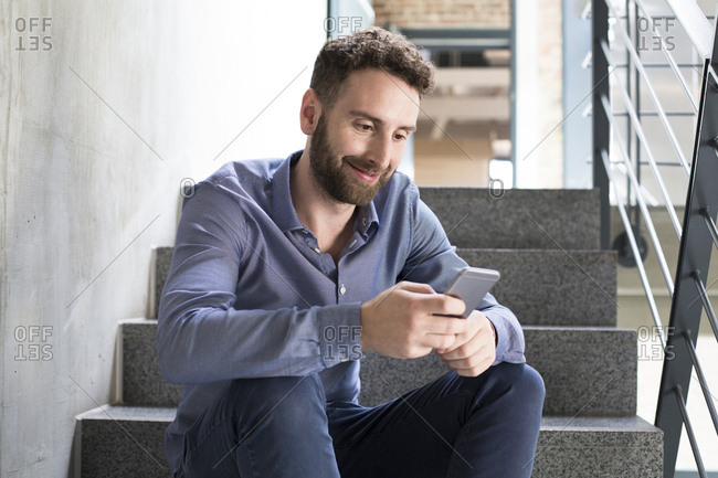 Smiling man sitting on stairs looking at cell phone
