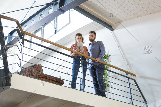 Colleagues standing on upper floor sharing tablet