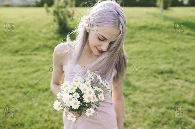Smiling woman with bunch of daisies on a meadow