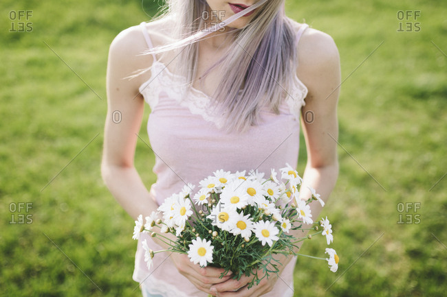 Woman holding bunch of daisies- partial view