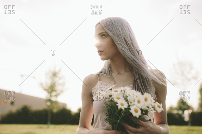 Woman with bunch of daisies at backlight