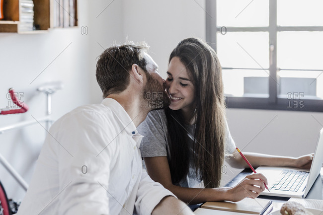 Happy couple with laptop at home kissing