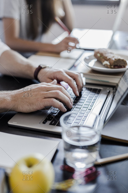 Hands of man using laptop at home