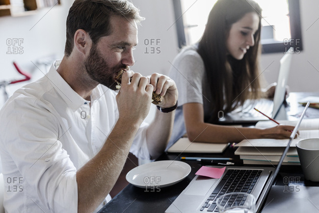 Man eating and woman using laptop at home