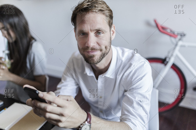 Portrait of smiling man at home using smartphone