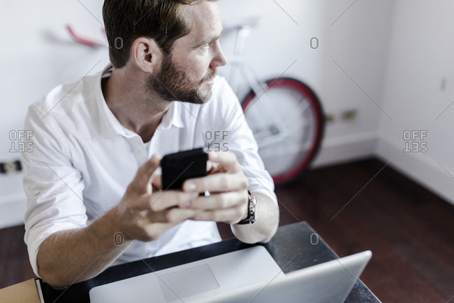 Man using smartphone and laptop at home