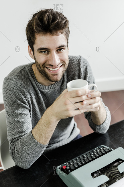 Portrait of smiling young man with typewriter