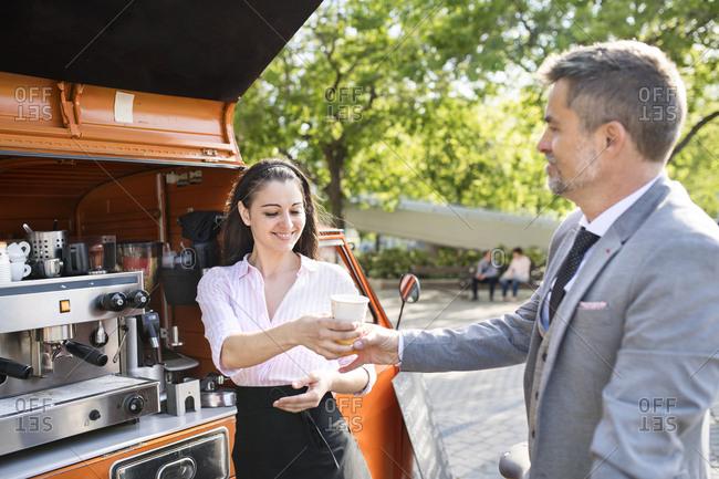Businessman buying take away coffee on the street
