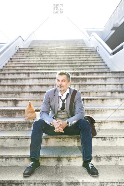 Confident businessman in the city sitting on stairs