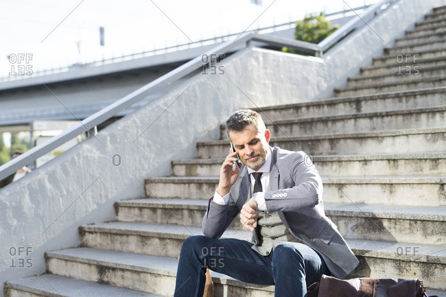 Businessman in the city sitting on cell phone checking the time