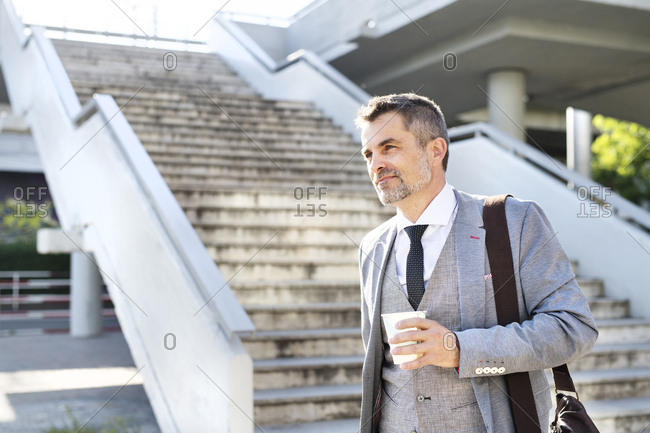 Confident mature businessman in the city with takeaway coffee