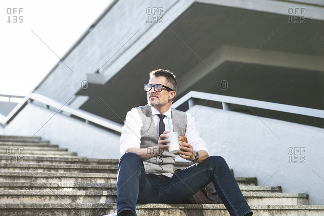 Businessman in the city sitting on stairs eating lunch