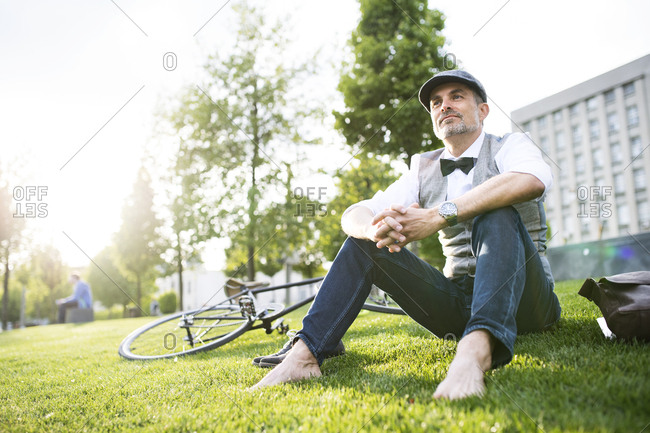 Mature businessman with bicycle in the city park sitting on grass