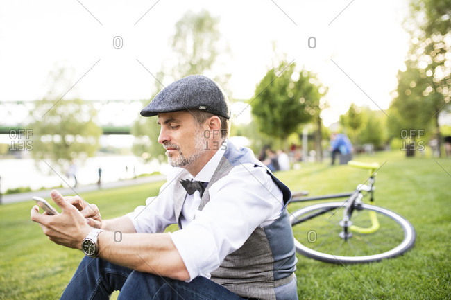 Confident mature businessman with bicycle and smartphone in the city park sitting on grass