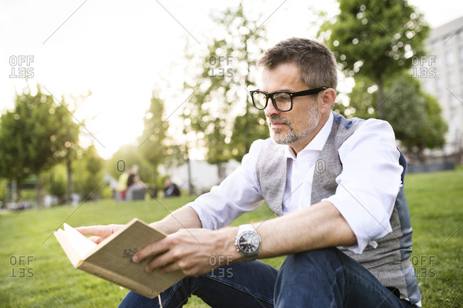 Confident mature businessman in the city park sitting on grass reading book