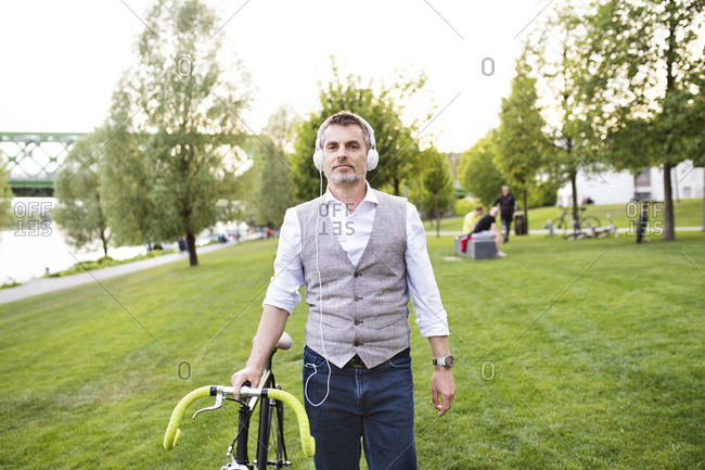 Confident mature businessman with bicycle and headphones in the city park