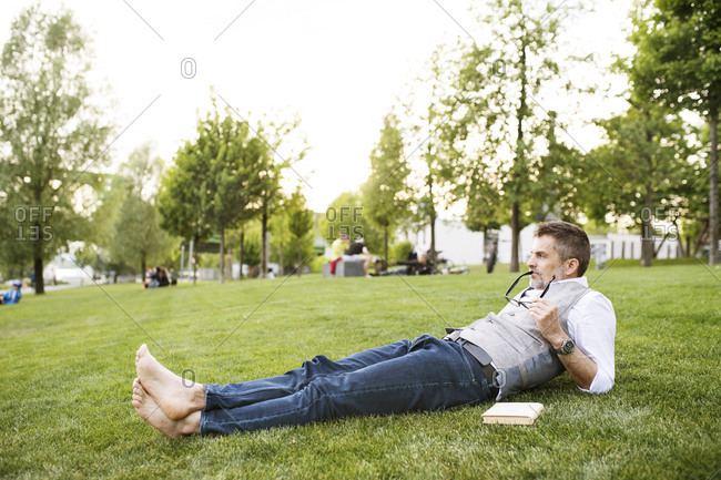 Mature businessman in the city park lying on grass